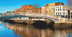 Dublin, panoramic image of Half penny bridge, or Ha'penny bridge, on a bright day with beautiful reflection of historic houses of the riverside in river Liffey