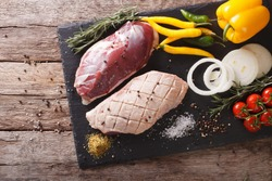 duck breast raw, with fresh vegetables and spices closeup on a cutting board. horizontal view from above