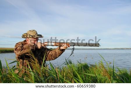 Duck hunter aims his gun