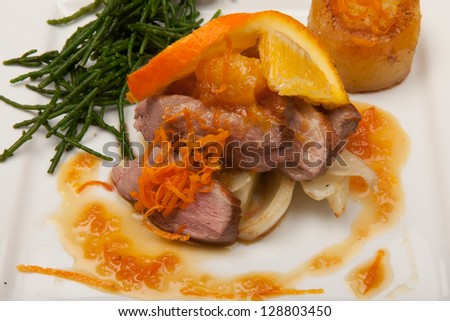 duck in orange sauce, traditional french dish on plate with garnish. Duck breast fried with oranges