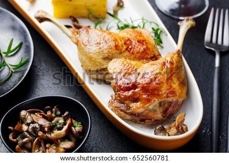 Duck legs confit with potato gratin and mushroom sauce. Close up.