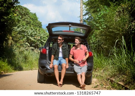 Dudes resting in back of car on road trip