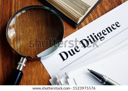 Due Diligence concept. Stack of documents and magnifying glass. Foto stock ©