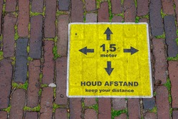 Due to Coronavirus disease (COVID-19) scourge, Yellow sign board on the brick footpath with Dutch word 1.5 meter, HOUD AFSTAND (1.5 meter, Keep your distance) Reminding peoples on street in Amsterdam.