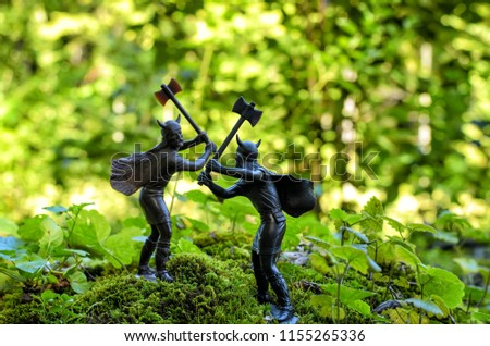 Duel (fight) of two Vikings with double-sided axes, standing on a hill covered with green moss and plants, vintage toy soldiers, blurry background with forest trees, Old Norse myths, norsemen theme