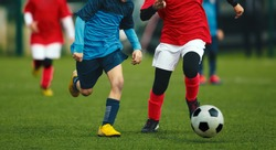 Duel of two young soccer players. Football match for kids. Training and football soccer tournament for children. Junior level soccer game. Footballers in red and blue jersey shirts. Autumn season
