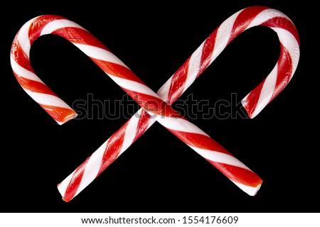 Duet of crossed barley sugars, on black background Stockfoto ©