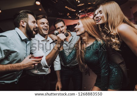 Duet. Trendy Nightclub. Have Fun. Ledy in Green. Dress. Background. Cheerful. Smile. Smiling Girl.Singing Songs. Handsome Men. Beautiful Girls. Friends at Karaoke Club. Karaoke Club. Celebration. #1268883550