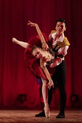 Duet young girl ballerina and a young man dancing ballet performance on stage in a theater