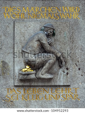 "Dukatenscheisser bas-relief on the wall of a Bank with text: ""This fable will probably never come true. The life teaches prudence and saving"", Dusseldorf, Germany"