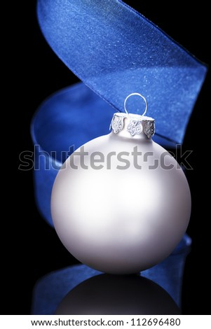 dull silver christmas ball in front of a blue ribbon on black background - stock photo