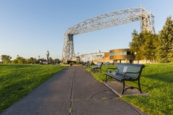 Duluth Canal Park - A sidewalk with park benches leading toward a lift bridge.