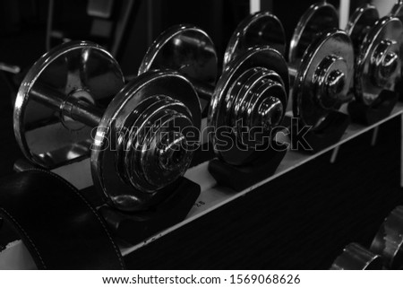 Dumbbell at the gym to build muscle. Dumbbells on empty floor in Gym. Fitness club weight training equipment. Black and white
