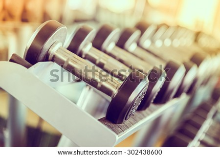 dumbbell in gym - vintage effect and sun flare filter effect