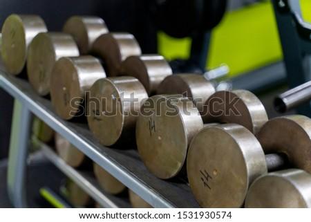Dumbbell set. Close up many metal dumbbells on rack in sport fitness center ,