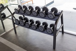 Dumbbell set. Many metal dumbbells on rack in sport fitness center. Weight Training Equipment concept.  Fitness equipment dumbbells weight for workout. Rows of dumbbells in the gym