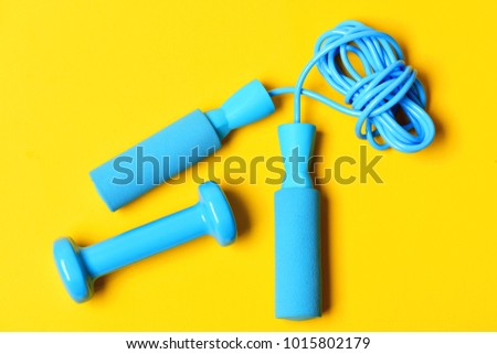 Dumbbell with jumping rope lay on yellow background. Healthy and active lifestyle concept. Sports equipment in cyan blue color. Gym and training tools. #1015802179