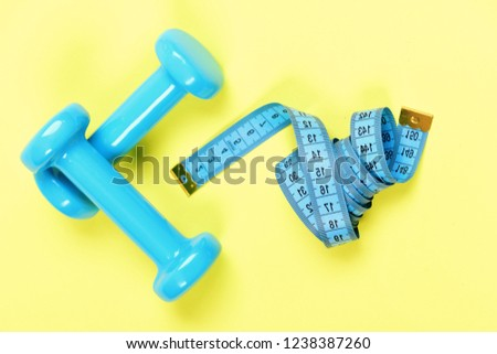 Dumbbells and measure tape in cyan blue color on light yellow background. Healthy shape and sport concept. Shaping and fitness equipment. Barbells next to roll of blue tape measure #1238387260