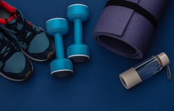 Dumbbells, fitness mat, water bottle and sneakers on classic blue background. Healthy lifestyle, fitness training. Color 2020. Top view. Flat lay