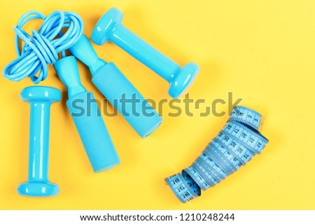 Dumbbells, jump rope and measuring tape lay top on yellow background. Weight loss and sports concept. Gym and healthy lifestyle tools. Centimeter and sport equipment in blue color. #1210248244