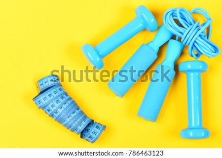 Dumbbells, jump rope and measuring tape lay top on yellow background. Weight loss and sports concept. Gym and healthy lifestyle tools. Centimeter and sport equipment in blue color. #786463123