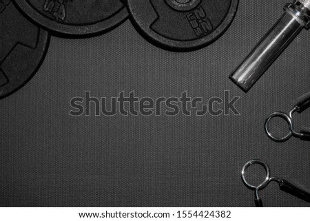 Dumbbells on carbon background. Dumbbells and weights are lying on the floor in the gym. Barbell set and gym equipment. Metal. Lift, coach