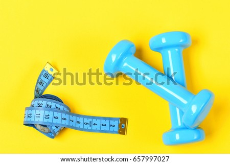 dumbbells or barbell and measuring tape on yellow background, exercise concept #657997027
