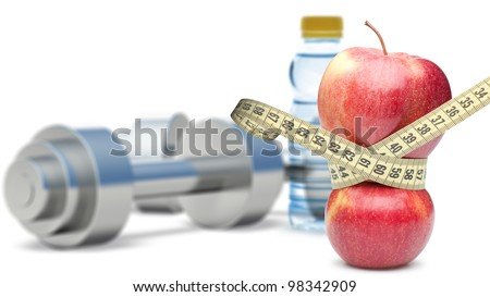 Dumbbells with an apple and measuring type. Dumbbells blured on a background. It is isolated on a white background - stock photo