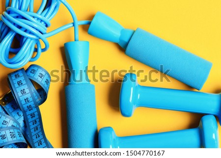 Dumbbells with centimeter and jumping rope lay top on yellow background. Sports equipment in cyan blue color. Healthy and active lifestyle concept. Gym and training tools.