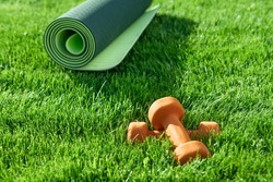 Dumbbells, yoga mat on a green lawn. Bright colors. Front view. Concept fitness outside, sport, healthy lifestyle, quarantine, home gym. Sunny day. Copy space. Nobody