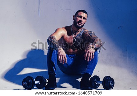 dumbell lifting. sexy abs of tattoo man. male fashion. muscular macho man with athletic body. brutal sportsman with barbell. steroids. confidence charisma. sport and fitness. strong guy exercising.