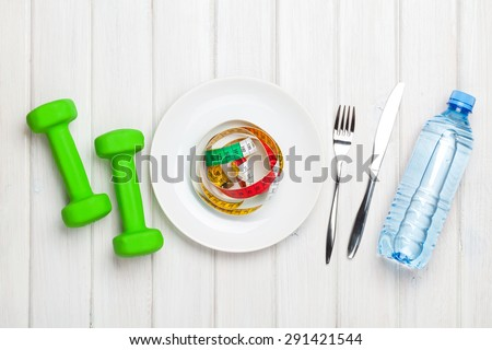 Dumbells and healthy food over wooden background. View from above