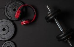Dumbells, red headphones on dark background.