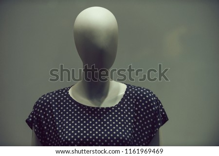 dummy imitating faceless woman in fashion blouse with no hair and makeup on grey background