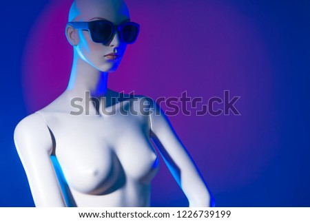 Dummy. Neon light. Artificial woman. Mannequin in black glasses. Female robot