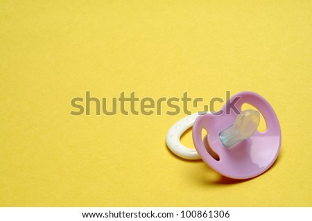 Dummy Pacifier on Yellow Background with Copy Space