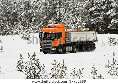 Dump-body truck on the road in winter woods