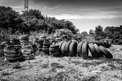 Dump of old tires of automobile wheels. Old wheel protectors. Old tyres polluting the nature. Environmental pollution.