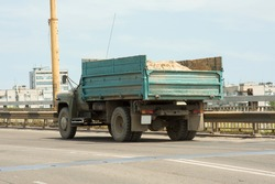 Dump truck transporting sand on a city highway