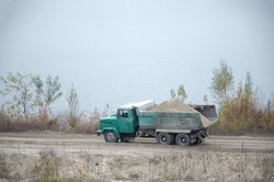 Dump truck transports sand and other minerals in the mining quarry. Heavy industry and resource transit