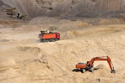 Dump truck transports sand in open pit mine. Excavator on the development of sand in a quarry. Mining industry concept