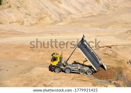 Dump truck unloading earth sand in quarry. Recovering the landscape around the open pit. Process of restoring land. Mine reclamation occurs once mining sand is completed. Stockfoto ©