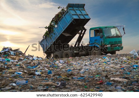 Dump truck unloading waste on a landfill #625429940