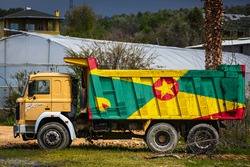 Dump truck with the image of the national flag of Grenada is parked against the background of the countryside. The concept of export-import, transportation, national delivery of goods