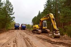 Dump trucks and excavator work on road construction in a forest zone. Tipper truck transport sand for roadworks project