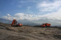 dump trucks at a construction site against the backdrop of a mountain landscape