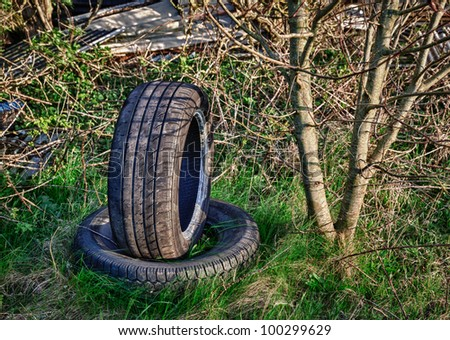 Dumped car tyres abandoned in overgrown field