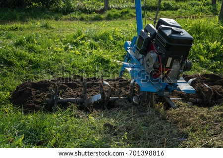 Dumping of land in the garden with a cultivator. #701398816