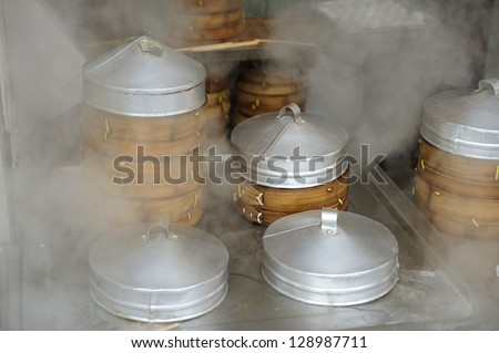 Dumplings cooking inside traditional bamboo steamers in outdoor restaurant in Shanghai