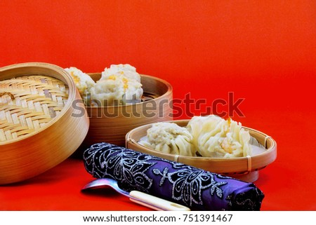 Dumplings served in bamboo containers with chili sauce, red background captured high angle/Dumplings in bamboo containers/Dumplings served in bamboo containers with chili sauce in red background #751391467